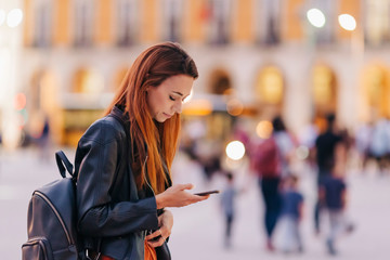 Young woman with backpack using smart phone on urban sidewalk
