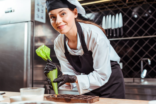 selective focus of happy chocolatier in black latex gloves holding pastry bag near chocolate molds