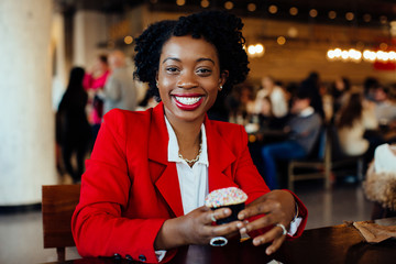 Portrait of a smiling, happy young woman sitting in a cafe holding a sprinkles covered cupcake, looking at camera