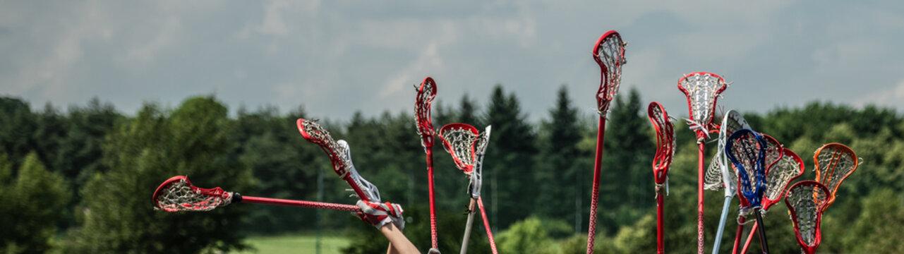 lacrosse raised lacrosse sticks against the sky