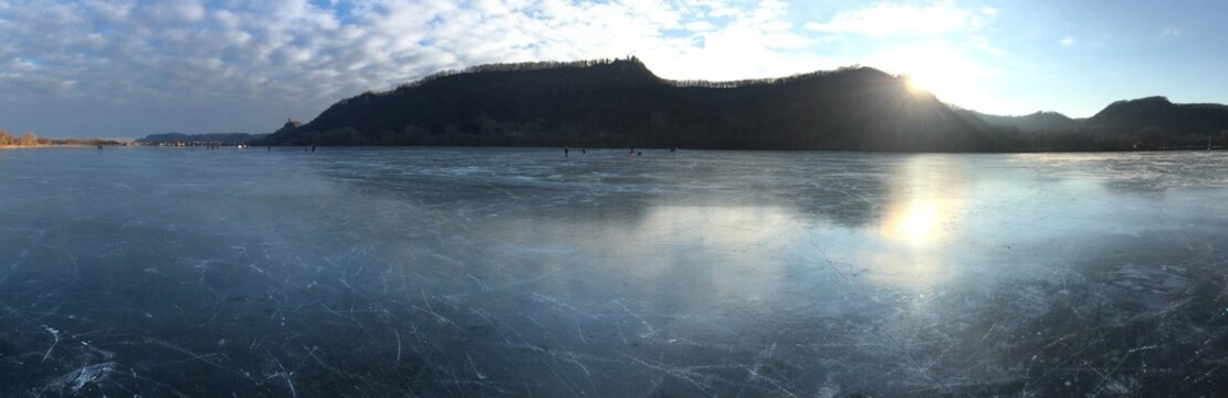 Sun setting over river bluffs with frozen lake in foreground (Winona, Minnesota)
