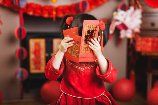 "Chinese baby girl  traditional dressing up with a ""FU"" means ""lucky"" red envelope"