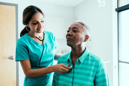 Nurse listening to stethoscope on patient's back