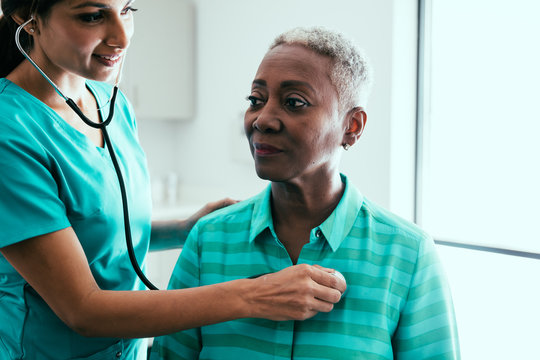 Nurse listening to stethoscope on patient's chest