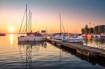 Boats docking in the marina at the Niegocin Lake during sunrise - Wilkasy, Masuria, Poland. Wall mural