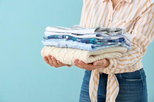Young woman with clean laundry on color background