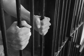 Prison Cell Bars.Hand of the prisoner holding steel lattice jail bars.Criminal justice imprisonment concept.