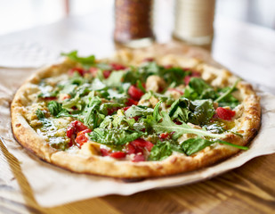 gourmet brick oven fired chicken and pesto pizza in restaurant