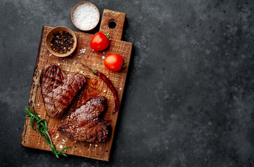 Tuinposter Steakhouse two grilled beef steaks in the form of a heart with spices for Valentine's day on a stone background with copy space for your text. dinner concept for two for Valentine's Day celebration