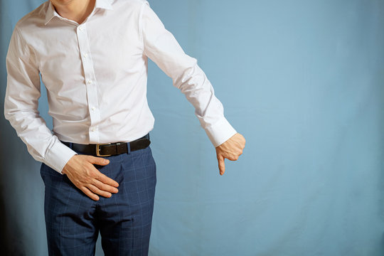 A man in trousers and a white shirt holds on to his groin, a symbol of prostatitis
