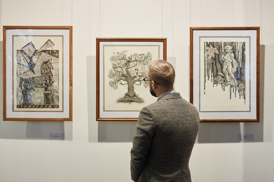 Rear view of young man in suit looking at modern art on the wall in museum