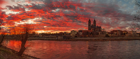 Foto auf Leinwand Osteuropa Panoramic view of beautiful bloody sunset in front of Cathedral of Magdeburg, downtown and river Elbe, Magdeburg, Germany, Winter, red cloudy sky