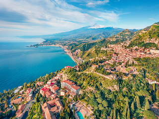 View from flying drone. Sunny morning view of Taormina town and Etna volcano on background. Nice spring seascape of Mediterranean sea. Splendid view of Sicily, Itale, Europe. Fototapete