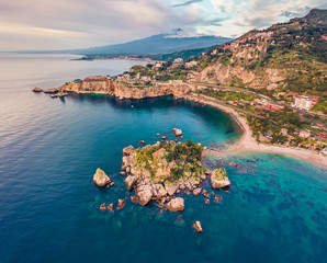 View from flying drone. Breathtaking morning view of Bella island and Etna volcano on background. Nice spring seascape of Mediterranean sea. Aerial view of Taormina town, Sicily, Itale, Europe.