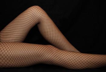 Beine einer Frau in Netzstrümpfen