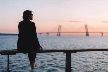 Alone dreamy woman with sunglasses and in black coat sitting on the edge of the sea. Female watching at colorful sunset. View from the back. Autumn scenic portrait. Copy space. Travel concept.