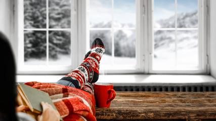 Woman legs and woolen winter socks.Blurred background of winter window.