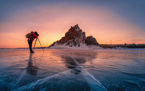 Photographer wear red clothes take photo of Shamanka rock at sunrise with natural breaking ice in frozen water on Lake Baikal, Siberia, Russia.