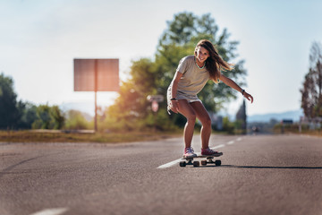 Sporty woman riding on the skateboard on the road. Longboarding, female.