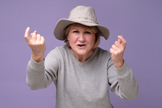 Angry or shocked mature woman in summer hat standing and looking at camera and screaming. Neighbor conflict concept