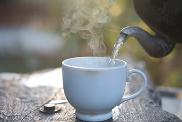 Pour hot water with smoke from a kettle. Fototapete
