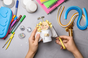 Woman making toy angel from toilet paper hub at grey table, top view