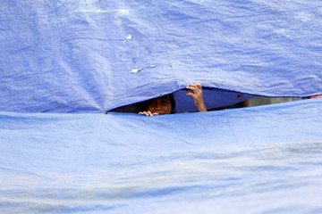A girl looks out between two tarps at a temporary shelter after floods in Jakarta