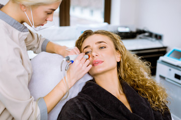 Face Skin Care. Professional female cosmetologist doing hydrafacial procedure in Cosmetology clinic. Hydra vacuum cleaner. Rejuvenation And Hydratation