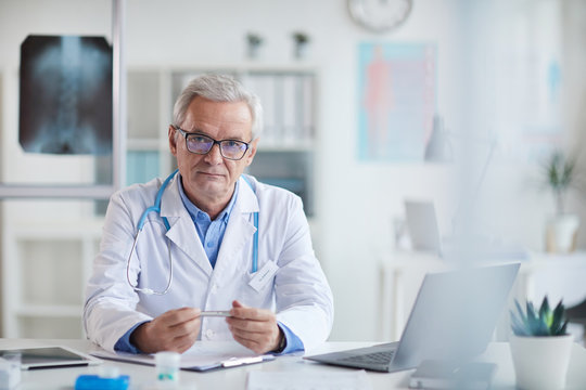 Portrait of serious senior doctor in eyeglasses and in white coat sitting at his workplace in front of laptop and looking at camera at office