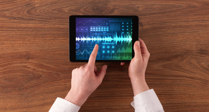 Hand touching tablet with waveforms and sound design concept