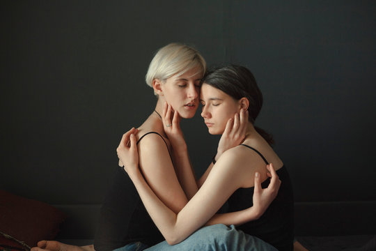 Couple with eyes closed cuddling each other indoors
