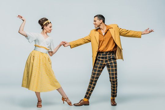 stylish dancers holding hands while dancing boogie-woogie on grey background