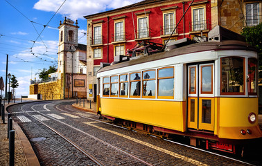 Lisbon Portugal. Yellow vintage tram driving by street of paving stones in district Alfama. Cityscape panorama with old houses and tower in sunny day with blue sky and white clouds. Wall mural