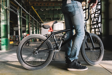 Young unrecognizable male staying with his bike on the ramp. BMX rider is performing tricks in indoor skatepark. BMX freestyle. Extreme sport.
