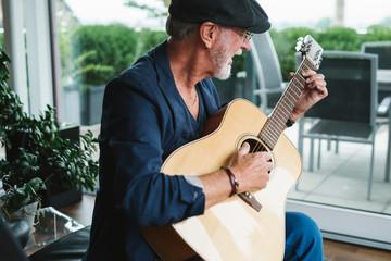 Happy active senior man playing a guitar at home