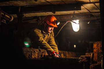 A tired miner in a coal mine looks at the light. Work in a coal mine. Portrait of a miner. Copy space.
