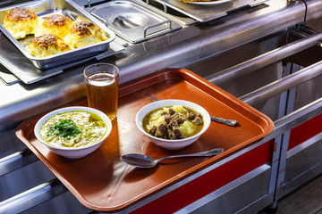 set with dishes and food on a tray in a public dining room, front and background blurred with a bokeh effect