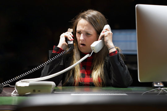 Portrait of office woman in stress. A lot of phone calls in office. An office worker female shouting in the phone's. Expression, emotions. Feelings problem reaction. Travel Agency Secretary.