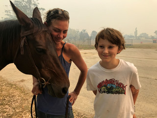 Bec Winter stands next to her son and her horse in Moruya