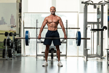 A strong muscular shirtless mature older bodybuilding athlete with balding gray hair  holding a heavy barbell, looking at camera in a gym