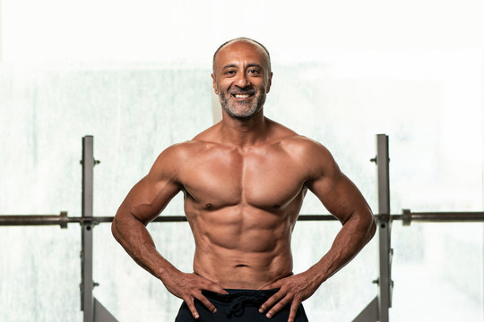Close up of  strong muscular shirtless mature older bodybuilding athlete with balding gray hair  with hands on hips smiling at camera in a gym