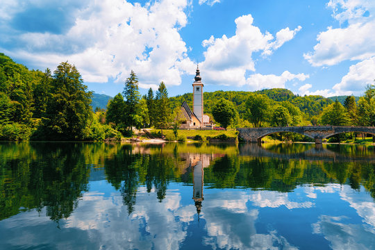 Scenery and Church of St John Baptist on Bohinj Lake at Slovenia. Nature in Slovenija. View of blue sky with clouds. Beautiful landscape in summer. Alpine Travel destination. Julian Alps mountains