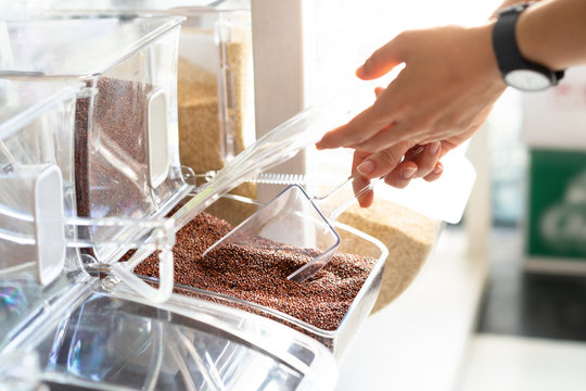 Closeup, Hands of woman scoop quinoa grains from clean refillable container in beautiful small business refill station. Healthy living, environmental friendly and zero waste lifestyle concept.