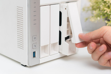 Closeup, a man's hand open one of drives arrays of personal NAS storage server and pull out hard disks to change in order to keep security, availability and accessibility of business data. Wall mural
