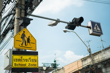 Yellow school zone warning sign at the roadside in Bangkok,Thailand.