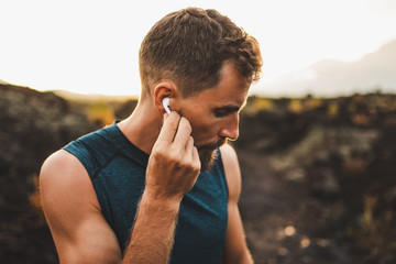 Man using wireless earphones air pods on running outdoors. Active lifestyle concept. Fotomurales