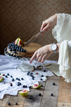Women hand with watch cutting rustic vegan zucchini cocoa cake topped with fresh summer fruits and peanut butter frosting in front of the vintage wallpaper on a wooden table with blueberries and figs
