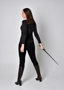 full length portrait of a pretty brunette girl wearing a black shirt and leather boots, holding a sword. Standing pose facing away and holding a sword,  on a grey studio background.