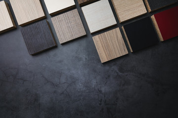 Obraz wood texture laminate furniture material samples on dark stone background with copy space - fototapety do salonu