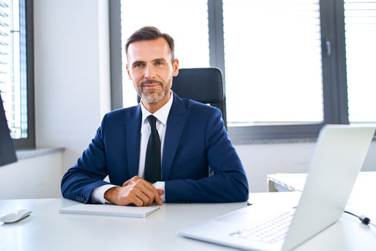 Smiling mature businessman sitting at office desk looking at camera